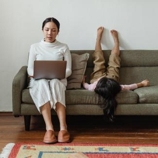 Woman sits on couch to work from home